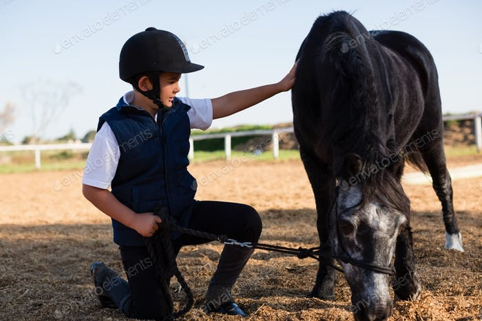 Boy holding the reins of a horse in the ranch