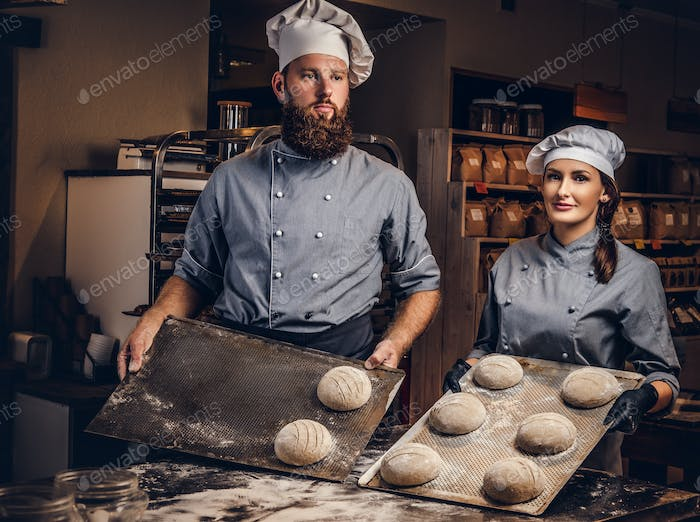 Chef with his assistant showing ready samples of baking test in kitchen.