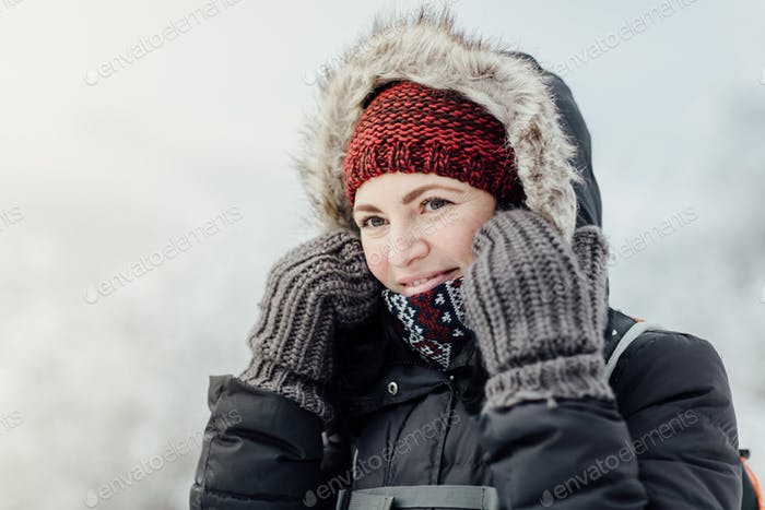 Thoughtful smiling woman dressed warm looking into distance