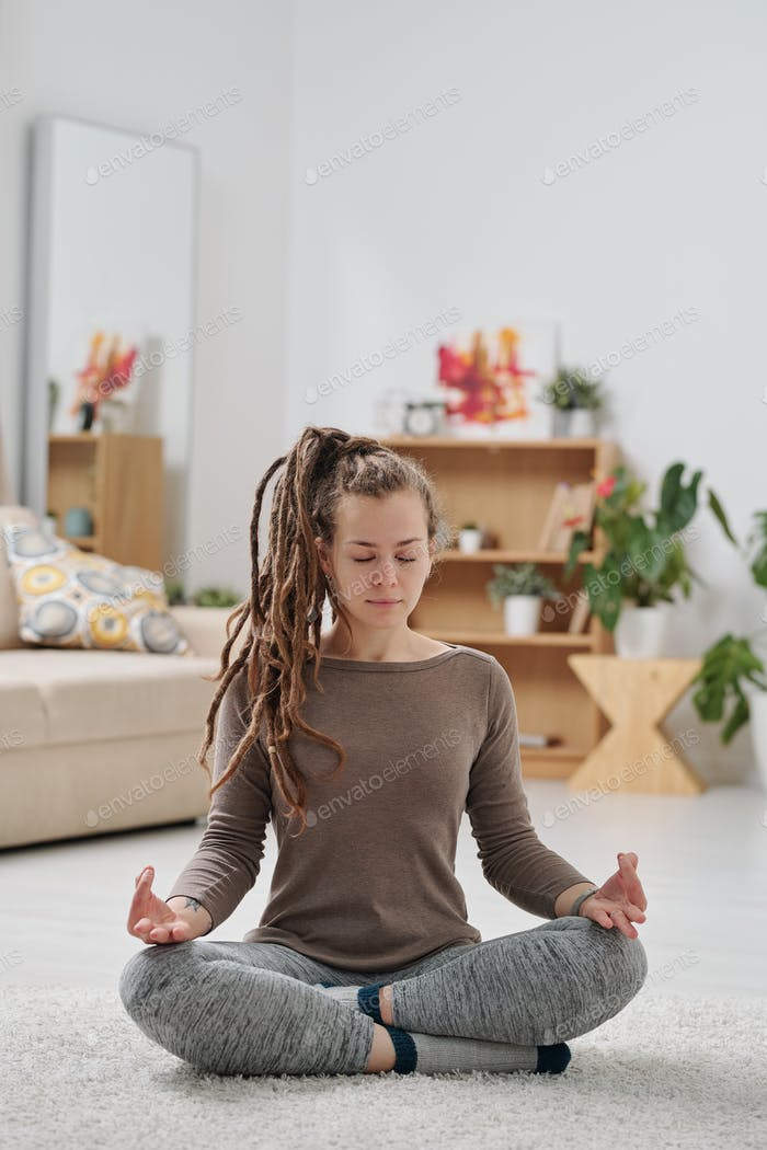 Pretty young active woman with dreadlocks sitting on the floor with crossed legs