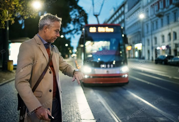 Mature businessman with suitcase waiting for a tram in the evening.