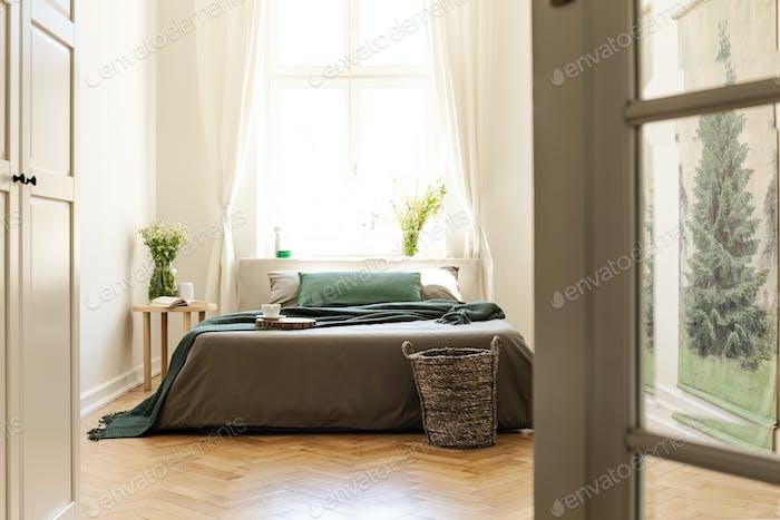 Green blanket on grey bed in minimal bedroom interior with flowe