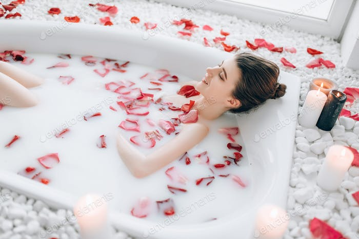 Woman sleeps in the bath with foam, rose petals