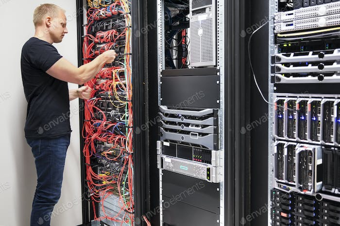 IT Consultant Working With Network Cables Connected To Servers