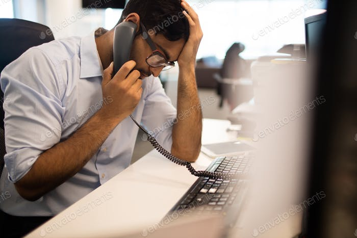 Tensed businessman talking on land line in office