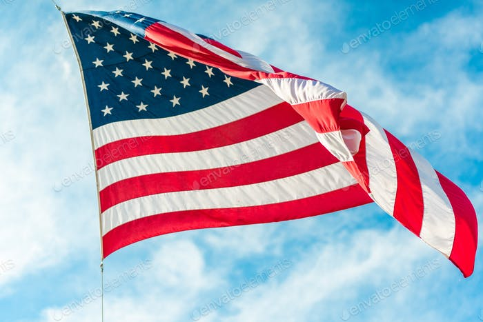 American flag waving in blue cloudy sky