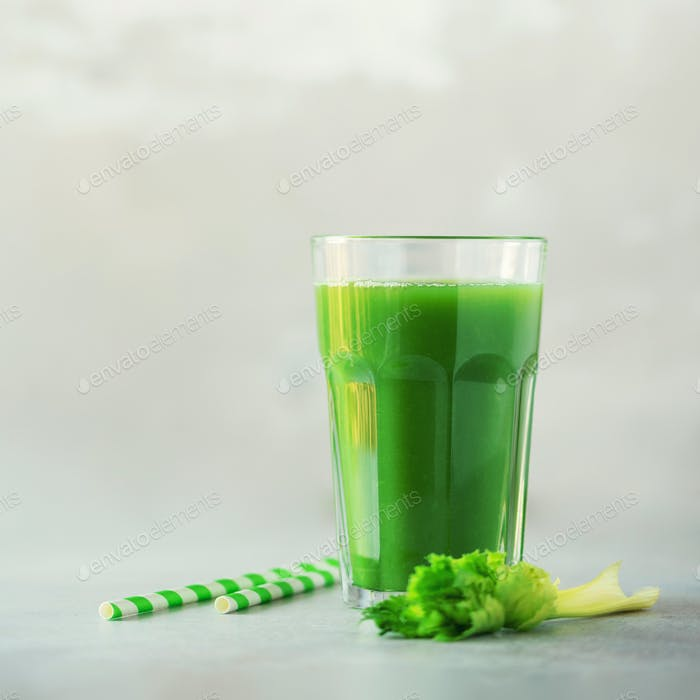 Glass of green celery smoothie on grey concrete background. Banner with copy space. Square crop