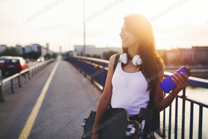 Portrait of beautiful smiling girl carrying skateboard