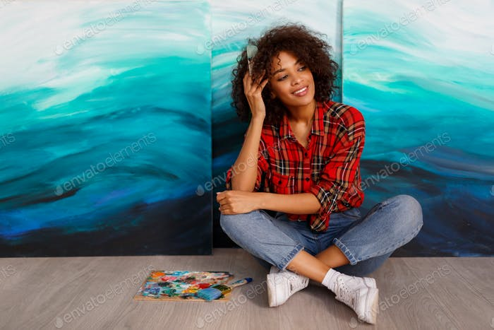 Portrait of a young african student sitting with amazing abstract sea acrylic hand drawn artwork