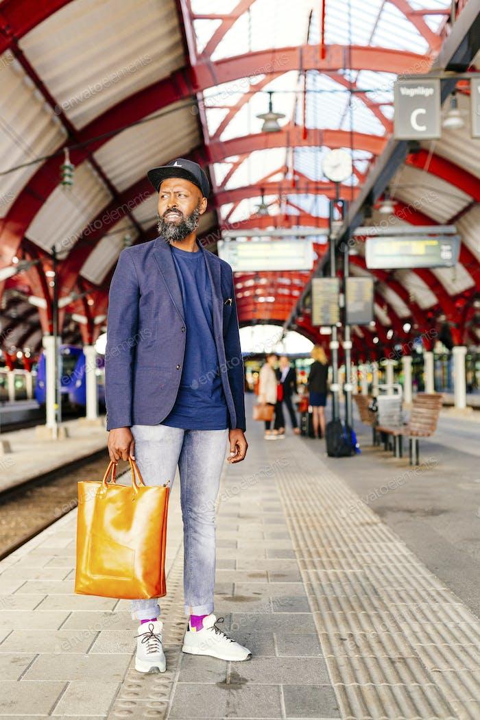 Полная длина вдумчивого бизнесмена, стоящего на железнодорожном вокзале