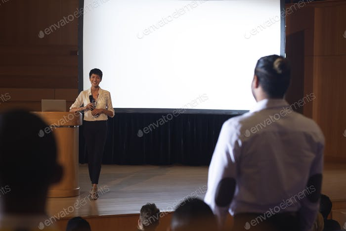 Businesswoman discussing while woman from the audience standing and asking query in the auditorium