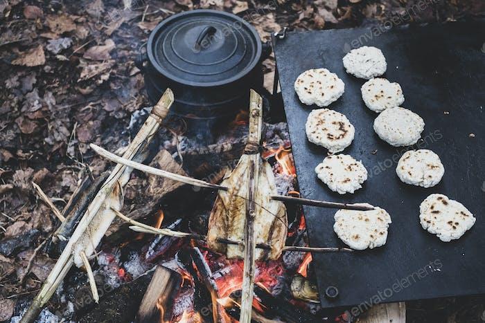 Hochwinkel Nahaufnahme von Fisch am Spieß und frisch zubereitete Brötchen über einem Lagerfeuer.
