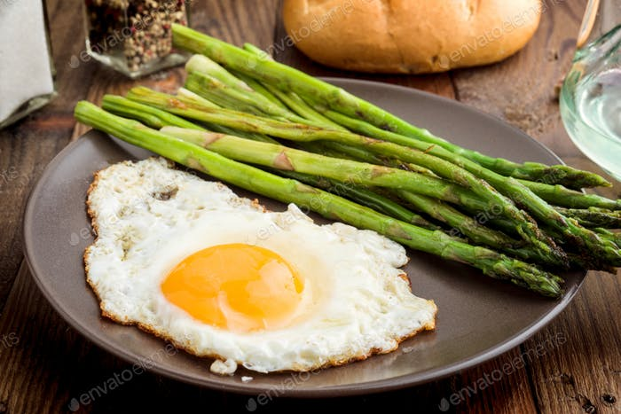 plate with fried egg and asparagus on barbecue on rustic wood