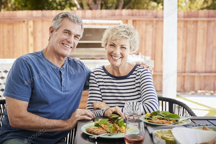 Senior white couple sit at lunch in garden looking to camera