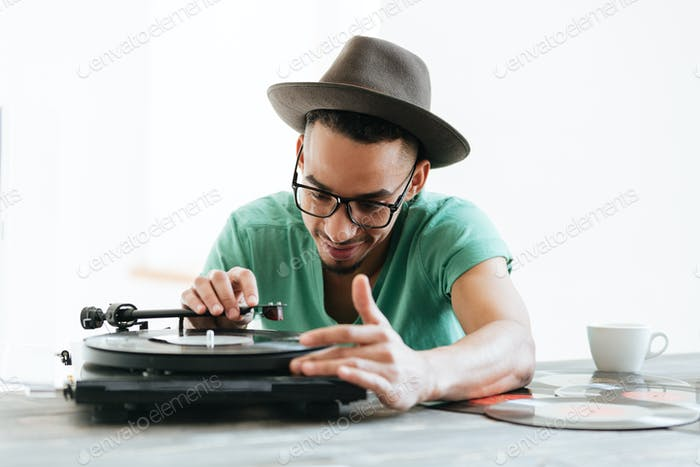 African man in t-shirt using record-player