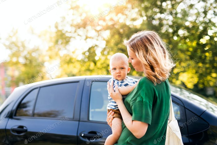 Young mother with her little baby boy standing by the car.