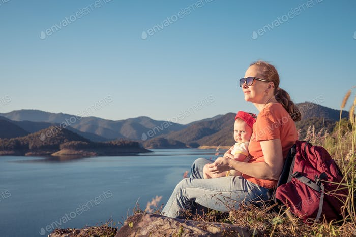 Happy family sitting near a lake at the day time.