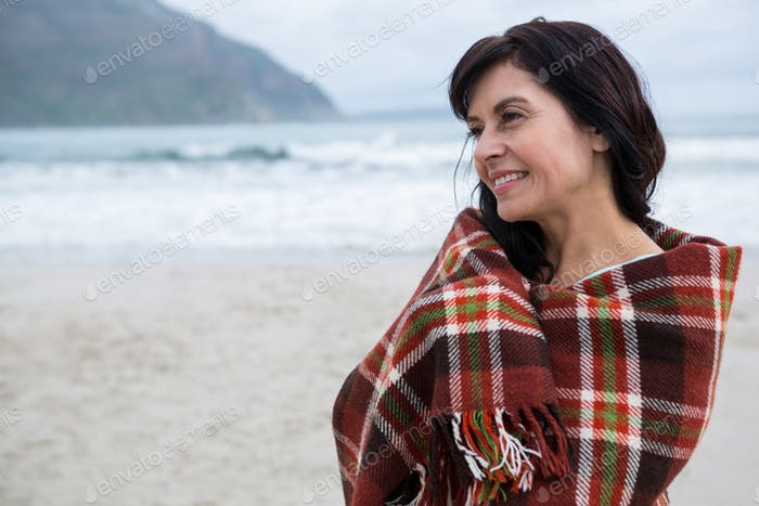 Happy woman wrapped in shawl on beach