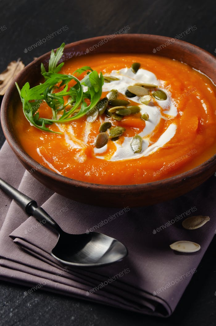 Tasty homemade rustic pumpkin soup with seeds in clay dish on slate tray