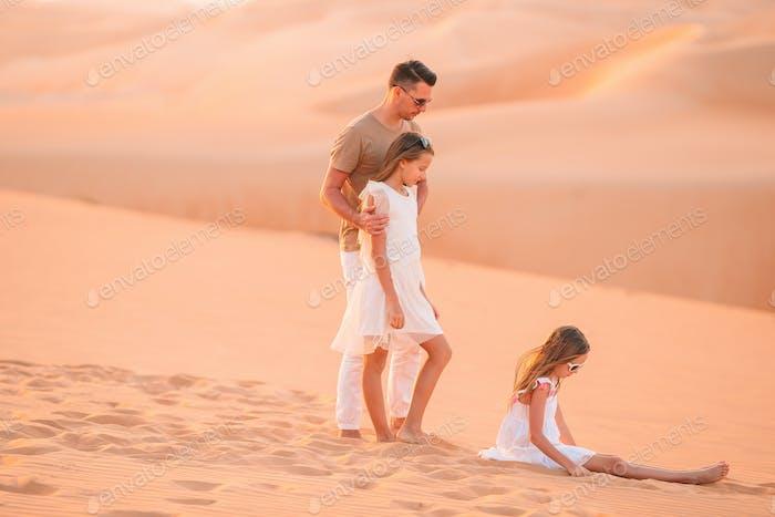Люди среди дюн в пустыне в Объединенных Арабских Эмиратах