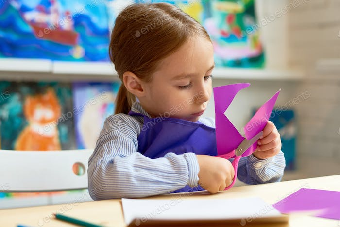 Cute Girl Cutting Out Paper Heart in Craft Class