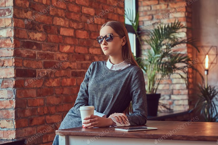 Ein junges schlankes sinnliches Mädchen in einem grauen Kleid und Sonnenbrille gelehnt