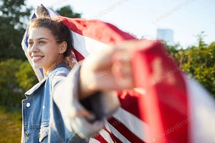 Pensive female patriot with US flag
