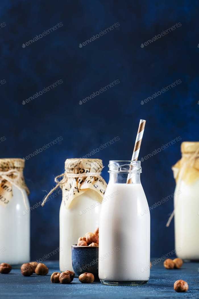 Vegan Hazelnut nut milk in bottles, closeup, blue table background