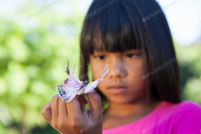 Cute little girl holding butterfly on a sunny day