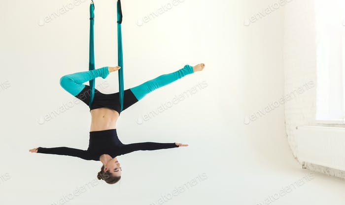 Woman practicing fly yoga over white background