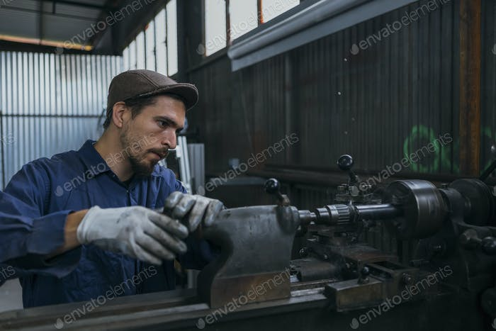 Bearded man working with iron machine