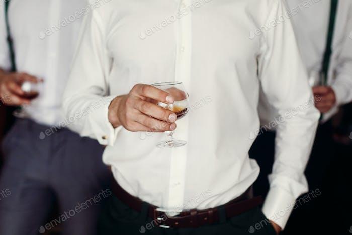 стильный красивый жених с грумсманом обнимает и держит виски в стекле