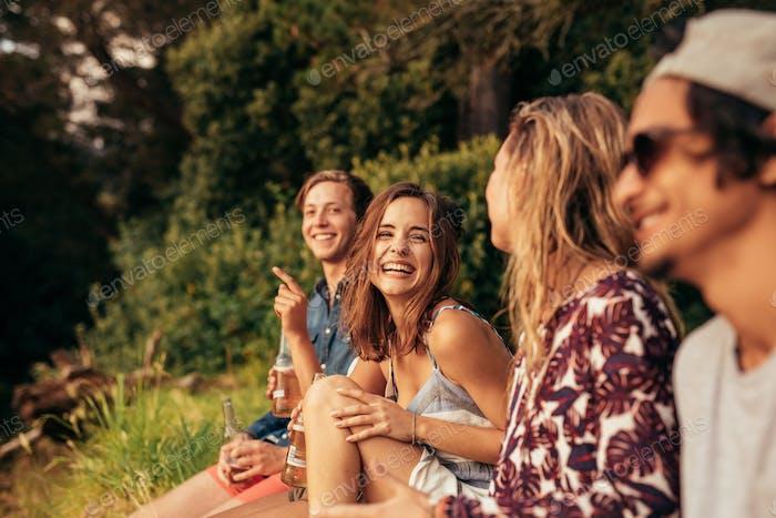 Fröhliche junge Freunde hängen mit Bieren
