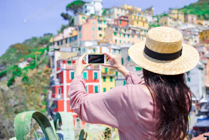 Young woman taking selfie background beautiful old italian village, Cinque Terre, Liguria