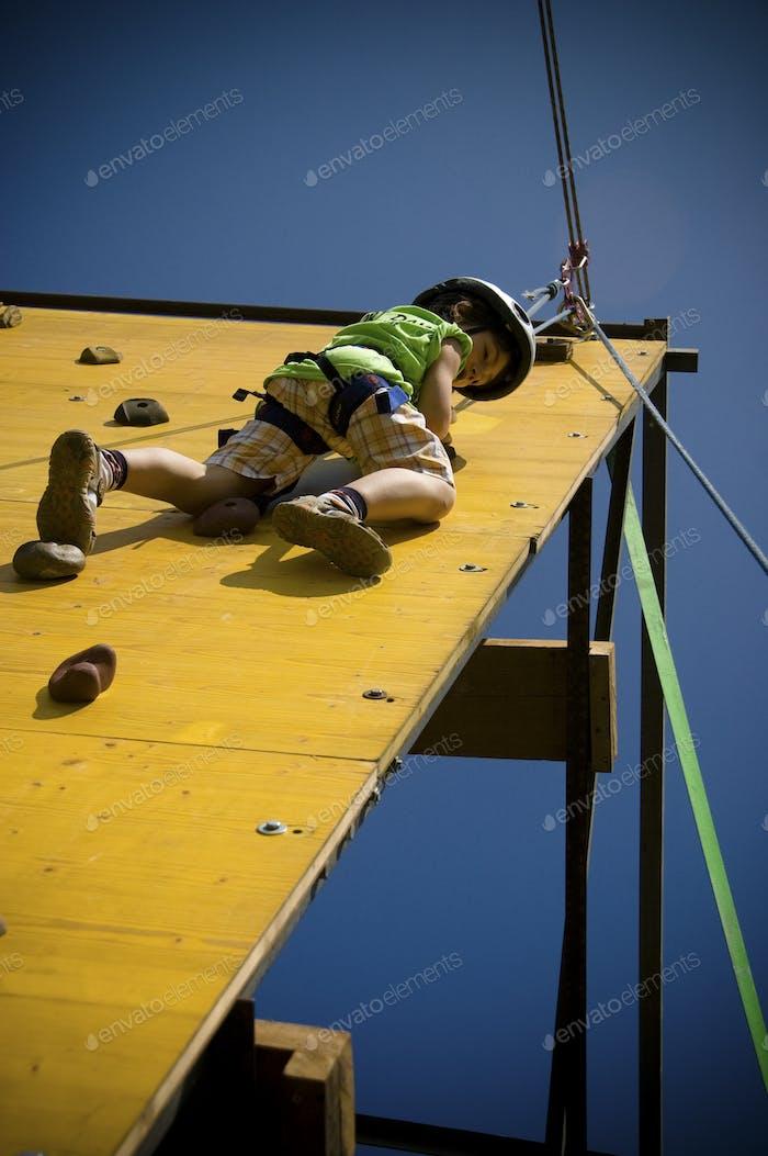 young climber boy climb a wall - kid have fun alone while he climb - enjoying moment