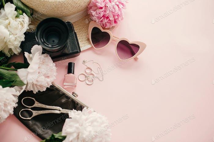 Stylish girly flat lay with pink peonies, photo camera, retro sunglasses, jewelry