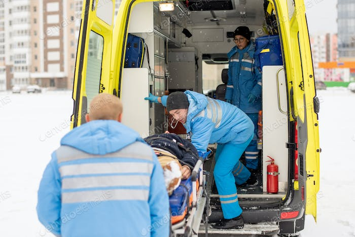 Paramedics getting stretcher with fixed unconscious man into ambulance car