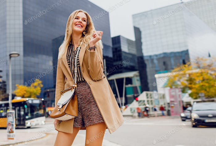 Blond woman with stylish accessories in spring casual outfit im big modern city.