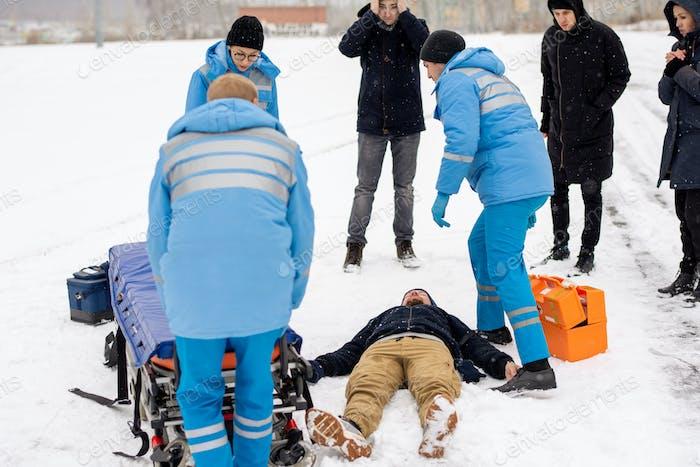 Brigade of young paramedics in uniform pushing stretcher towards unconscious man