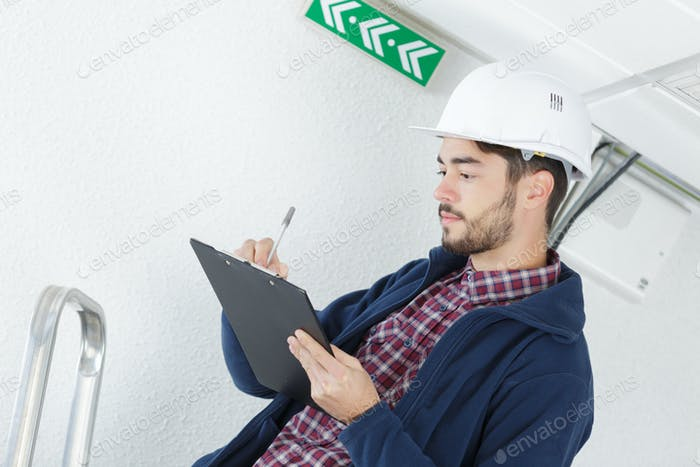 Inspector in hardhat writing on clipboard
