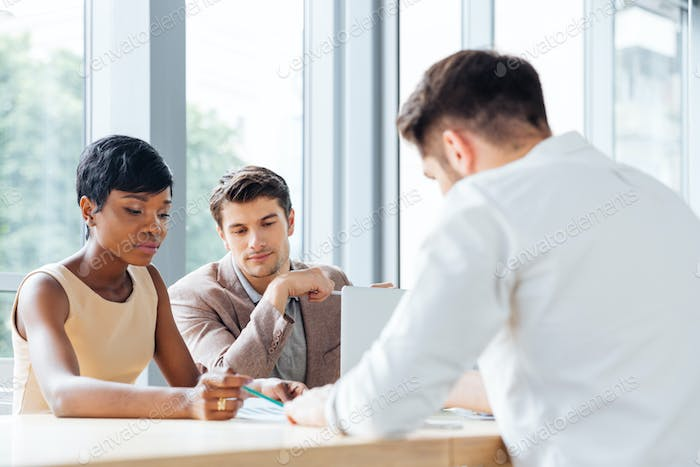 Businesspeople sitting at table and working together in conference room