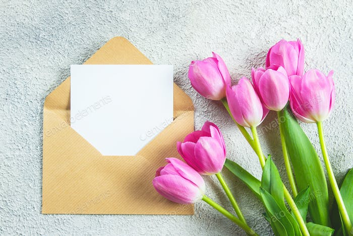 Mother's day Holiday Concept. Pink tulips flowers and empty card on concrete background.
