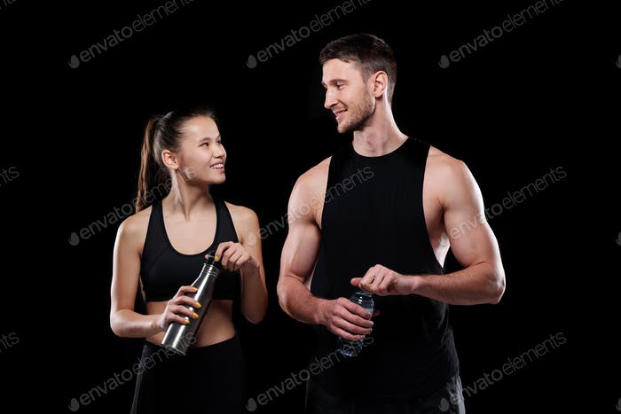 Cheerful girl and sportsman with bottles of water looking at one another