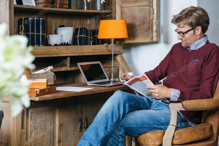 Hombre joven en silla leyendo periódico
