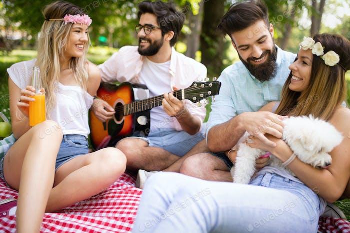 Glückliche junge Freunde mit Picknick im Park