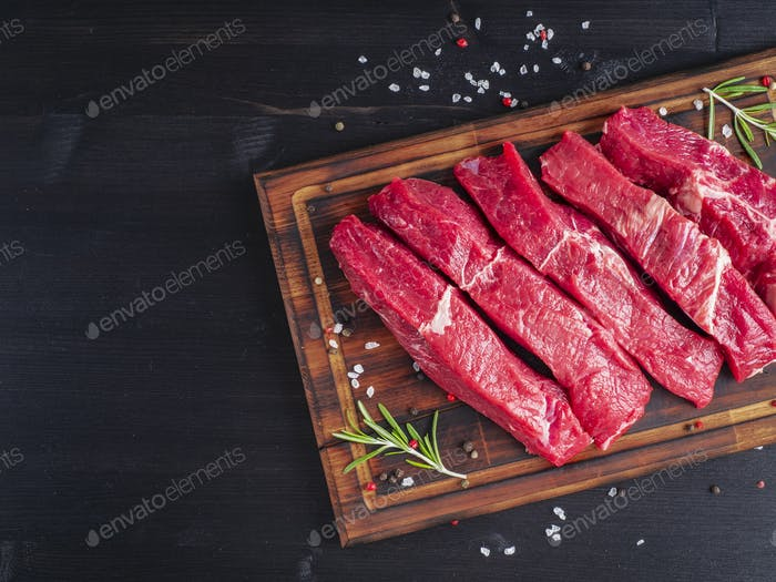 Raw meat, beef steak with seasoning on chopping board on dark background with rosemary,