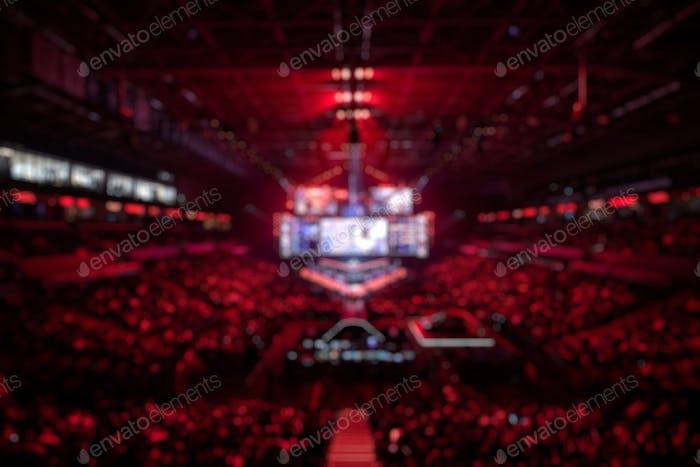 Verschwommener Hintergrund eines eSports-Events - Hauptbühne, große Leinwand und Lichter vor dem Start von