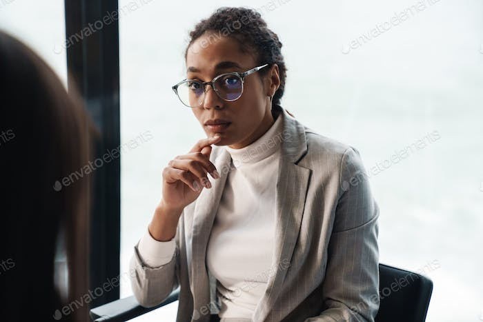 Portrait of young brunette businesswomen during job interview in office