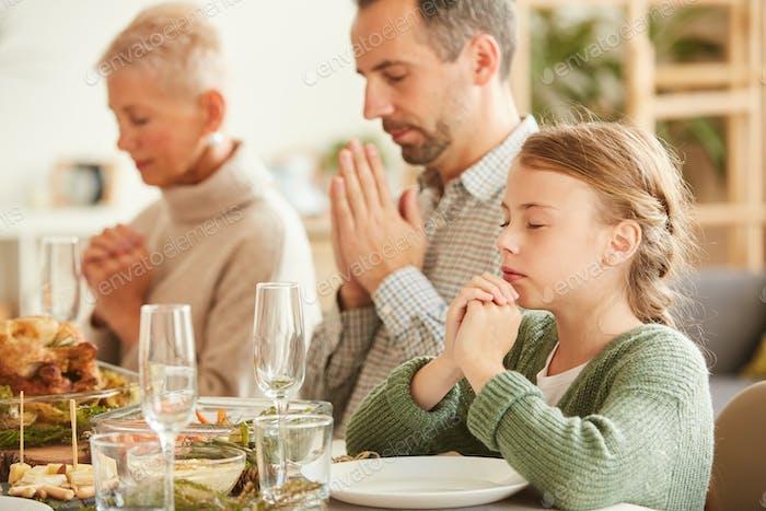 Familie dankt Gott für das Essen