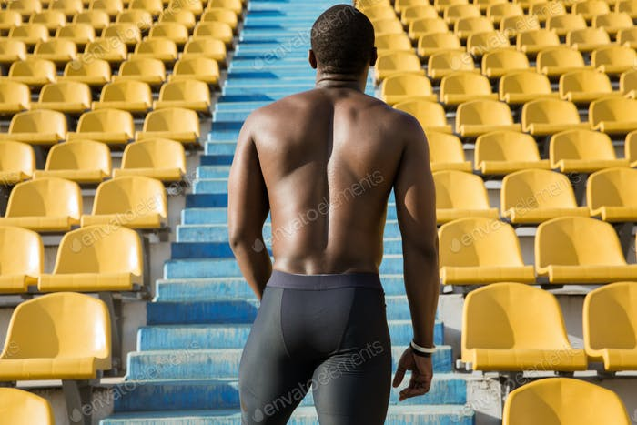 Back view of a muscular sportsman ready to start running